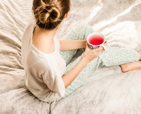 mujer en actitud relajada y bebiendo una infusion como uno de los habitos de vida saludable