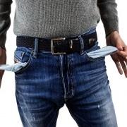 hombre sacando el forro de sus bolsillos en señal de que no tiene dinero