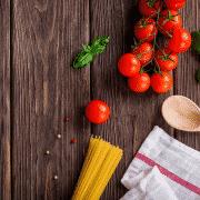 tomates, albahaca, spaghetti, una cuchara de madera y un paño sobre una mesa de madera