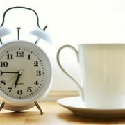 Reloj despertador junto a taza de desayuno