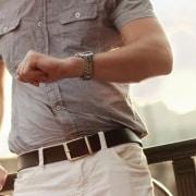 Hombre con camisa mira su reloj analógico