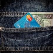 bolsillo de un jean con una tarjeta y un billete de 100 dólares