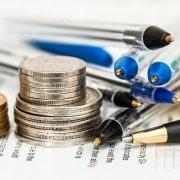 Monedas y bolígrafos apilados sobre unos documentos