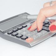 Mujer con uñas rojas utilizando una calculadora