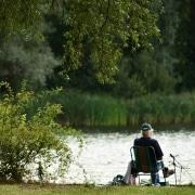 Jubilado sentado junto a un bonito lago
