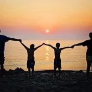 Una familia de cuatro integrantes juntas bajo una puesta son en una playa