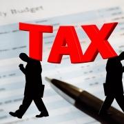 Silueta de dos personas junto a un bolígrafo y letras en rojo que muestran la palabra tax