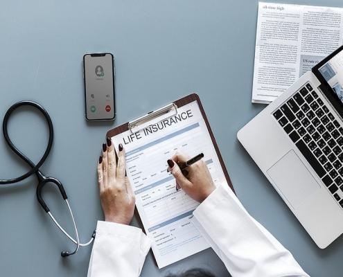 doctora rellenando el seguro de vida en su despacho