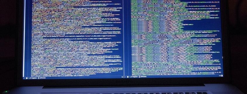 Ordenador en el que se muestran líneas de código informático