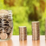 Bote de cristal lleno de monedas junto a monedas apiladas