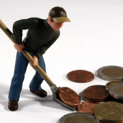muñeco recogiendo monedas con una pala para ahorrar