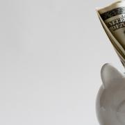 Hucha de cerdito color blanco para ahorrar dinero con billetes de dolar