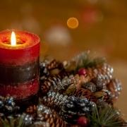 Vela roja encendida sobre centro de mesa navideño