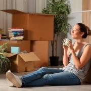 chica sentada en el suelo rodeada de cajas de mudanza bebiendo de una taza
