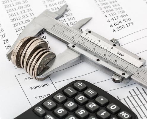 Calibre midiendo un conjunto de monedas sobre unas facturas y una calculadora