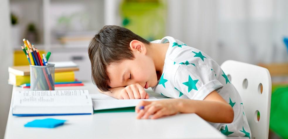 Niño con camiseta de estrellas dormido sobre su brazo en un escritorio