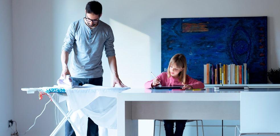 Hombre planchando junto a una niña escribiendo en una tableta electrónica