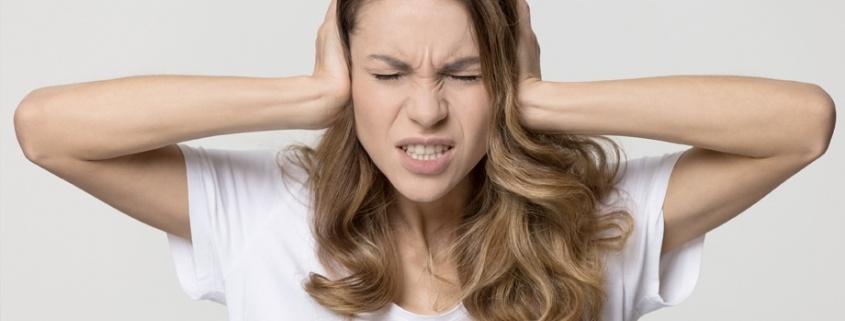 Mujer se lleva las manos hacia sus oídos señal de que le molesta el ruido
