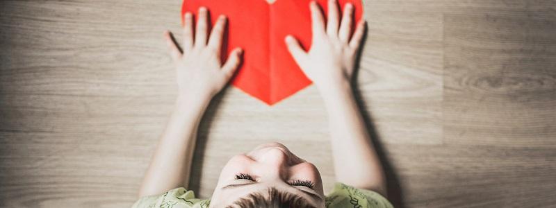 niño con un corazón de cartulina en las manos