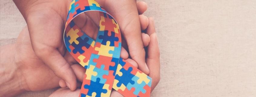 Cuatro manos sostienen el lazo del día del autismo