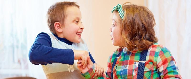 Dos niños autistas cruzan sus manos mientras se miran
