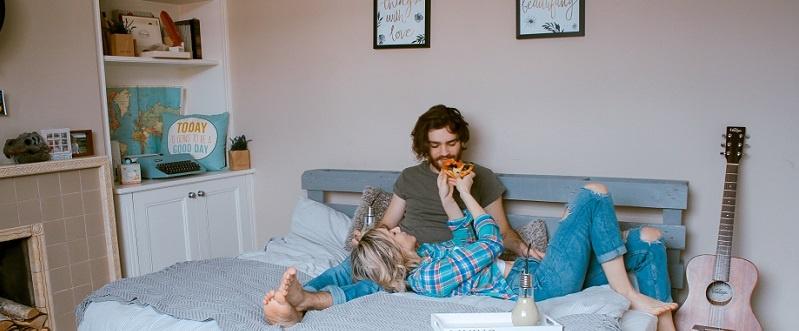 Pareja de jóvenes sobre una cama comiendo pizza