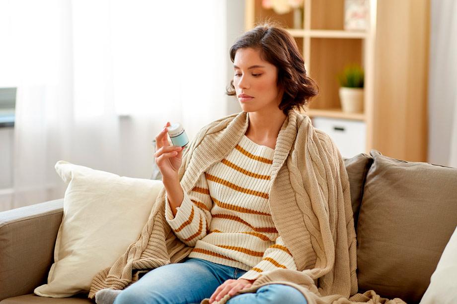 mujer sentada en un sofá mirando un bote de pastillas