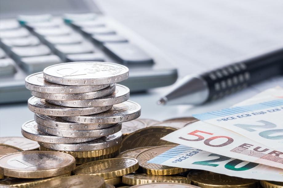 torre de monedas junto a billetes, un boli y un teclado