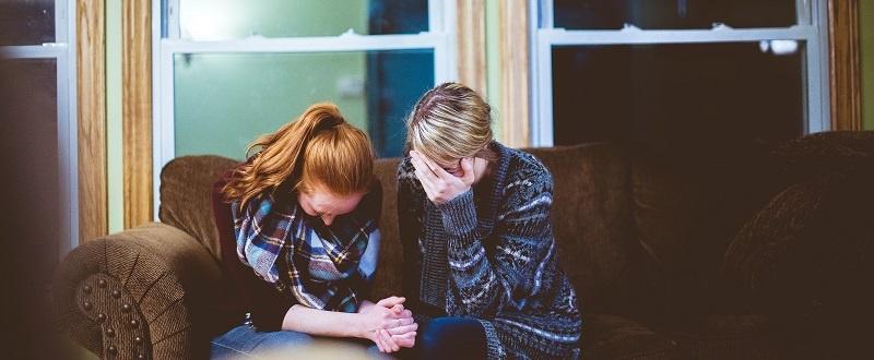 Dos mujeres lloran desconsoladas en un sofá de color marrón