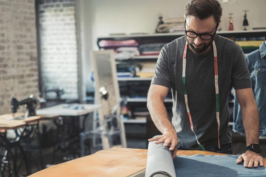 Hombre con gafas desenrollando una tela en un taller de costura