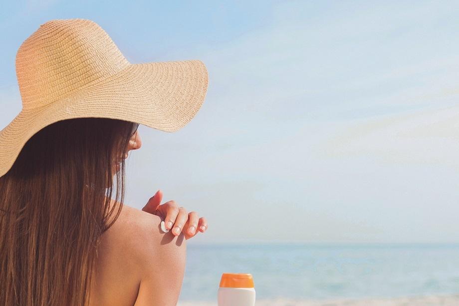 mujer echándose crema para evitar alergia al sol