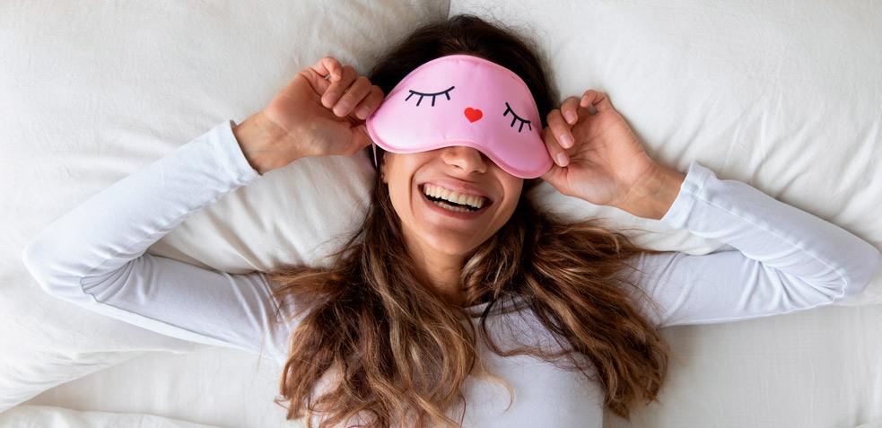 mujer tumbada en la cama, con los ojos tapados por un antifaz rosa y cara de felicidad