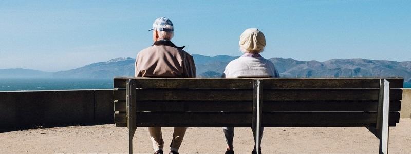 pareja de jubilados sentados en un banco mirando al horizonte juliación españa