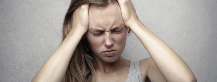 Mujer joven levándose las manos a la cabeza signo de cefalea