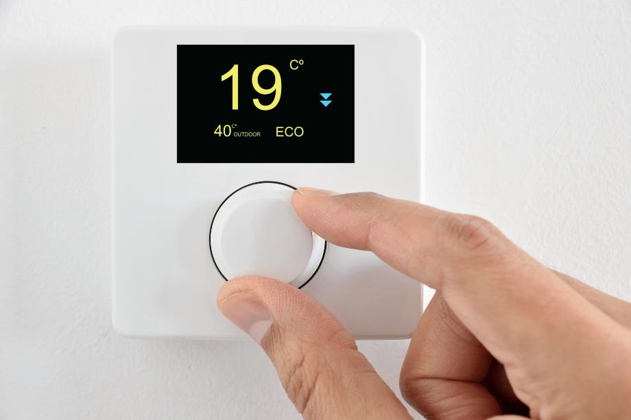 Persona utiliza un centro de control de calefacción de su vivienda