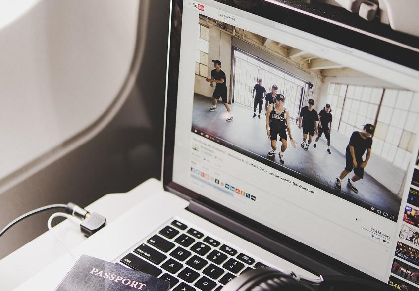 Ordenador portátil en el que se ve Youtube, debajo un pasaporte y unos cascos.