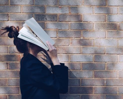 Mujer con libro tapándose la cara