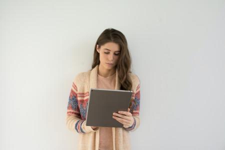 Mujer joven de pelo castaño lee en una tableta electrónica frente a una pared