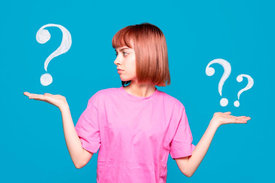 Mujer pelirroja con camiseta rosa frente a un fondo azul con signos de interrogación
