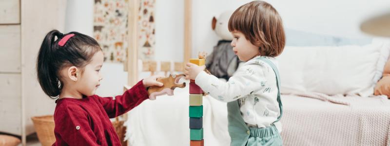 Niños jugando con unos cuadrados de colores en una habitación